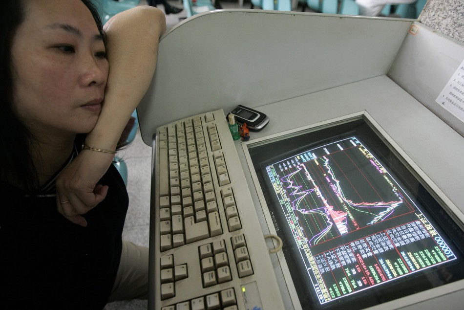 A woman watches the Shanghai Composite Index on computer screen in Shanghai