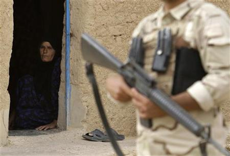 A woman looks at an Iraqi soldier standing guard