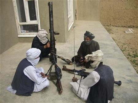 Taliban fighters pose with weapons as they sit in their compound at an undisclosed location in southern Afghanistan