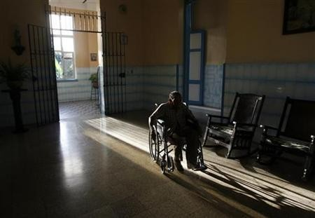 An elderly man rolls along in his wheelchair at the Santovenia Asylum in Havana July 6, 2009.