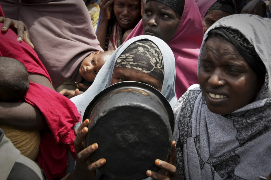 A woman covers her face with a cooking pot as she queues for food in a camp established by the Somali Transitional Federal Government for the internally displaced people in Mogadishu