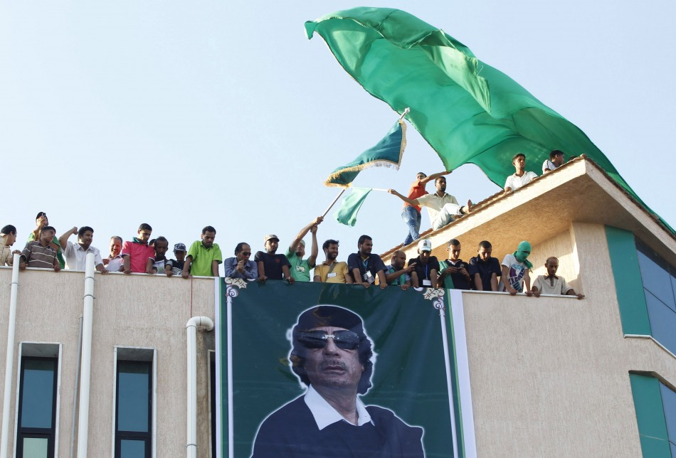 Supporters of Libya's leader Muammar Gaddafi look on during a rally in the town of Al-Ajaylat