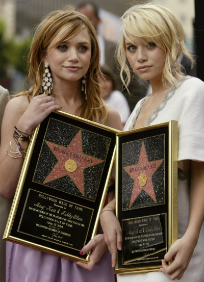 OLSEN TWINS POSE AFTER RECEIVING STAR ON HOLLYWOOD WALK OF FAME.