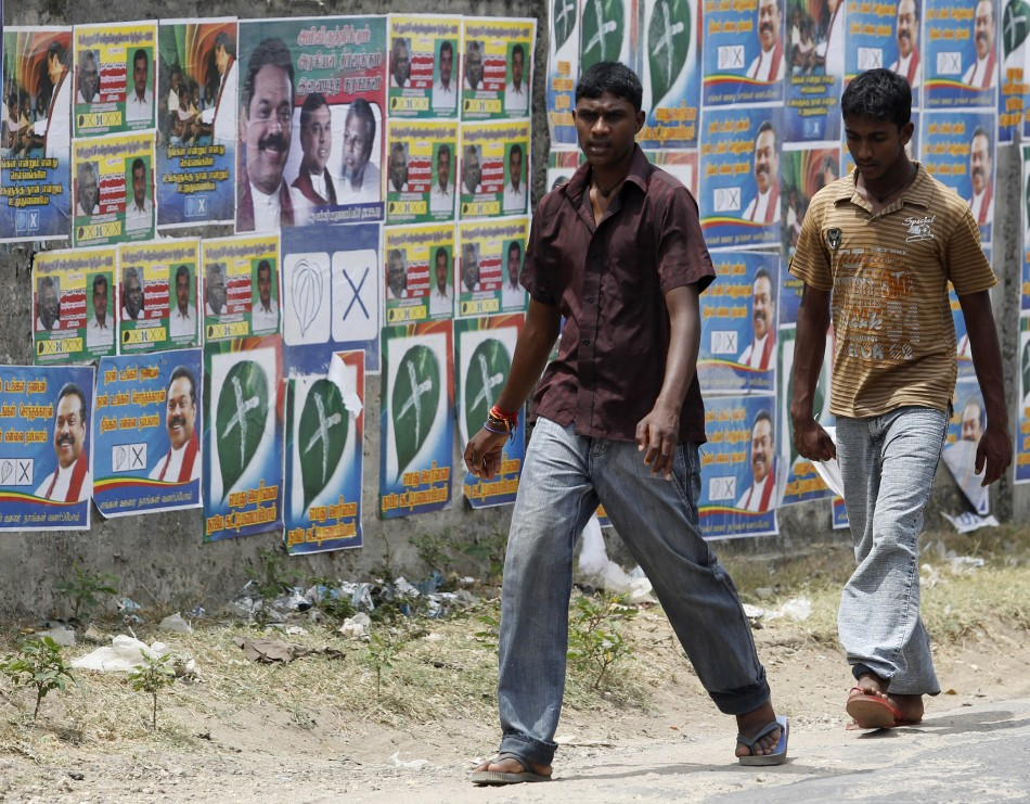 Two boys walk past local government election campaign posters in Jaffna