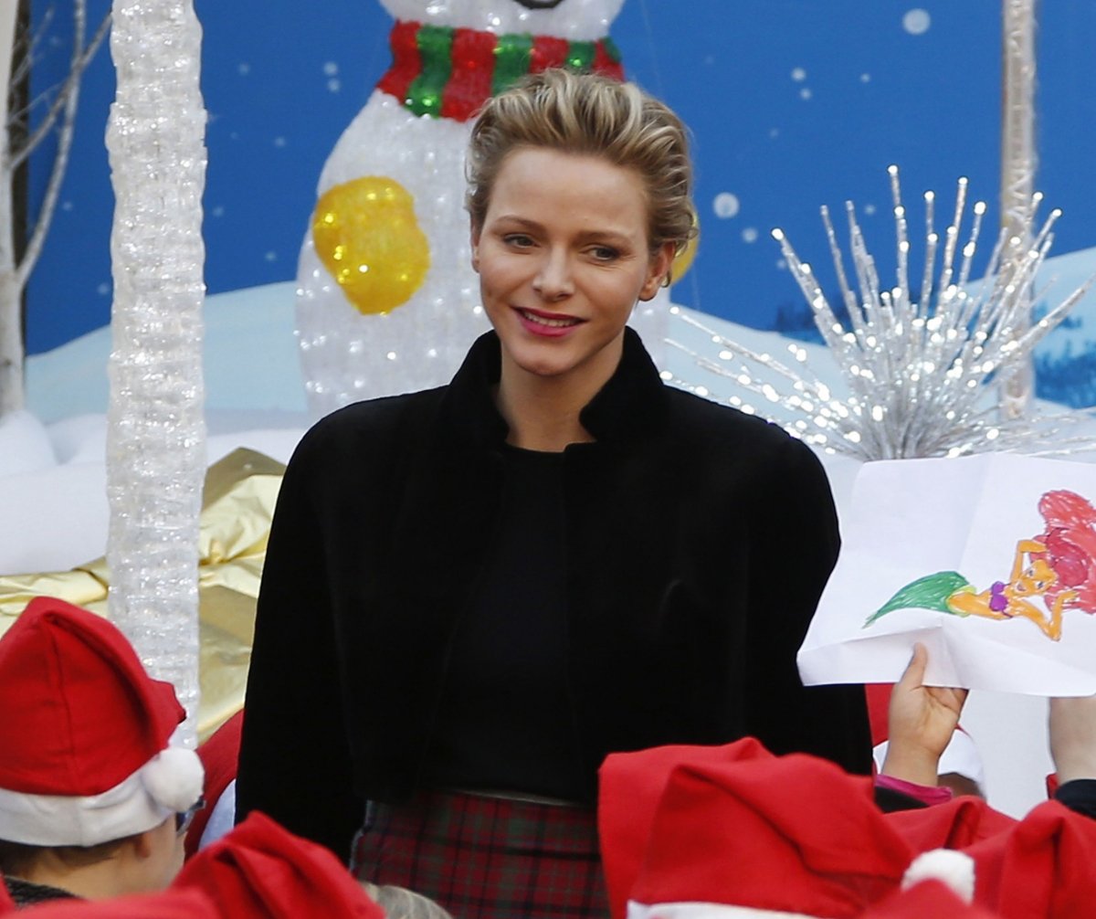 Princess Charlene of Monaco poses with children during the traditional Christmas tree ceremony at the Monaco Palace as part of Christmas holiday season in Monaco December 18, 2013.