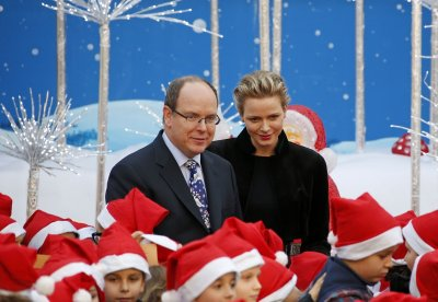 The royal couple of Monaco pose with children during Christmas tree ceremony.