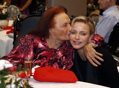 Princess Charlene of Monaco is kissed by a woman during a gift ceremony in the gerontology service at the Princess Grace Hospital.
