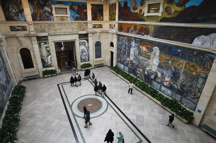 People at a mural by artist Diego Rivera at the Art Institute of Detroit in Detroit, Michigan December 3, 2013
