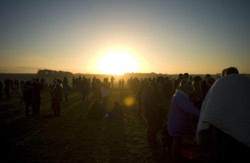Revellers gather as they enjoy the sunrise during the winter solstice at Stonehenge.