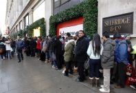 Shoppers queue outside Selfridges on London\'s Oxford Street.
