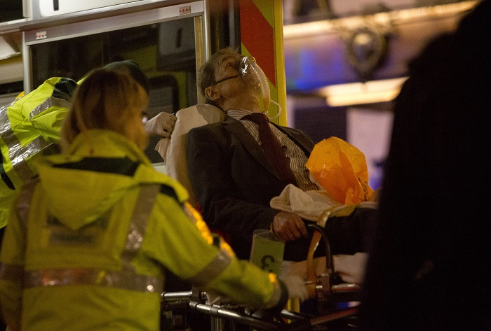 A man injured during the Apollo Theatre's ceiling collapse receives medical attention from paramedics.
