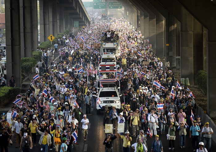Thousands of demonstrators march through Bangkok's streets shouting anti-government slogans.