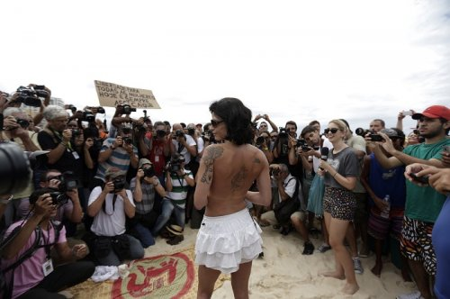 A topless protester poses in front of photographers on Brazil's Ipanema beach.