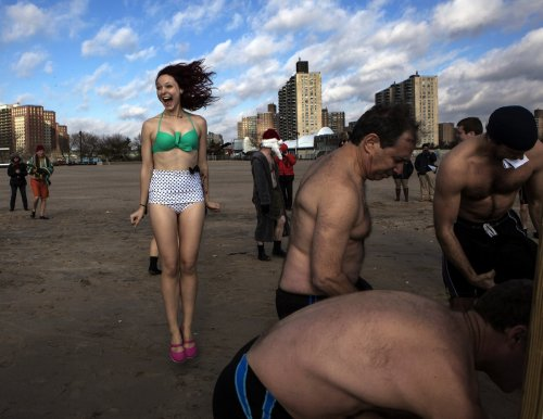 Hardy holiday revellers don't let the freezing conditions stop their fun at the Coney Island Polar Bear Club, swimming at the beach at Coney Island in New York.
