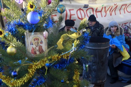 The demonstrations don't stop for Christmas in Ukraine. Pro-European integration protesters warm themselves near a stove and a Christmas tree during a rally in Independence square in Kiev.