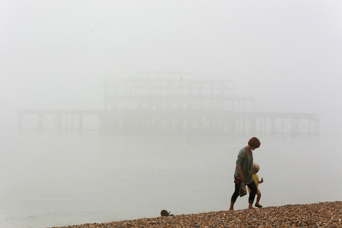 A woman and child walk on the beach in Brighton, UK.