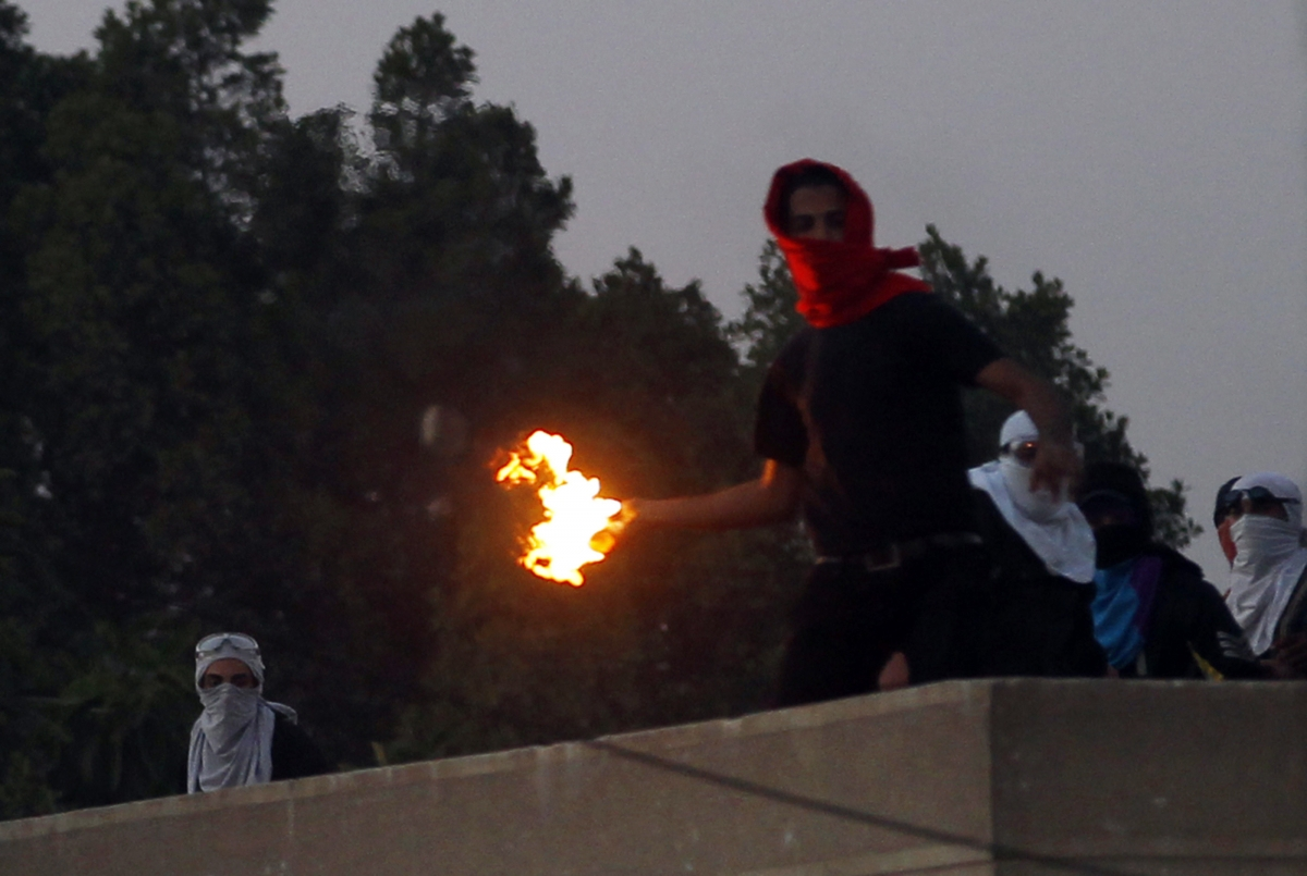 A masked student of Al-Azhar University throws a Molotov cocktail at riot police and residents during clashes outside the university campus in Cairo