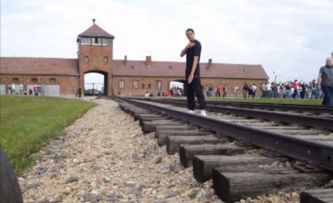 A young man performs the gesture outside Auschwitz concentration camp. (YouTube)