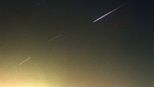 A meteor streaks across the night sky.
