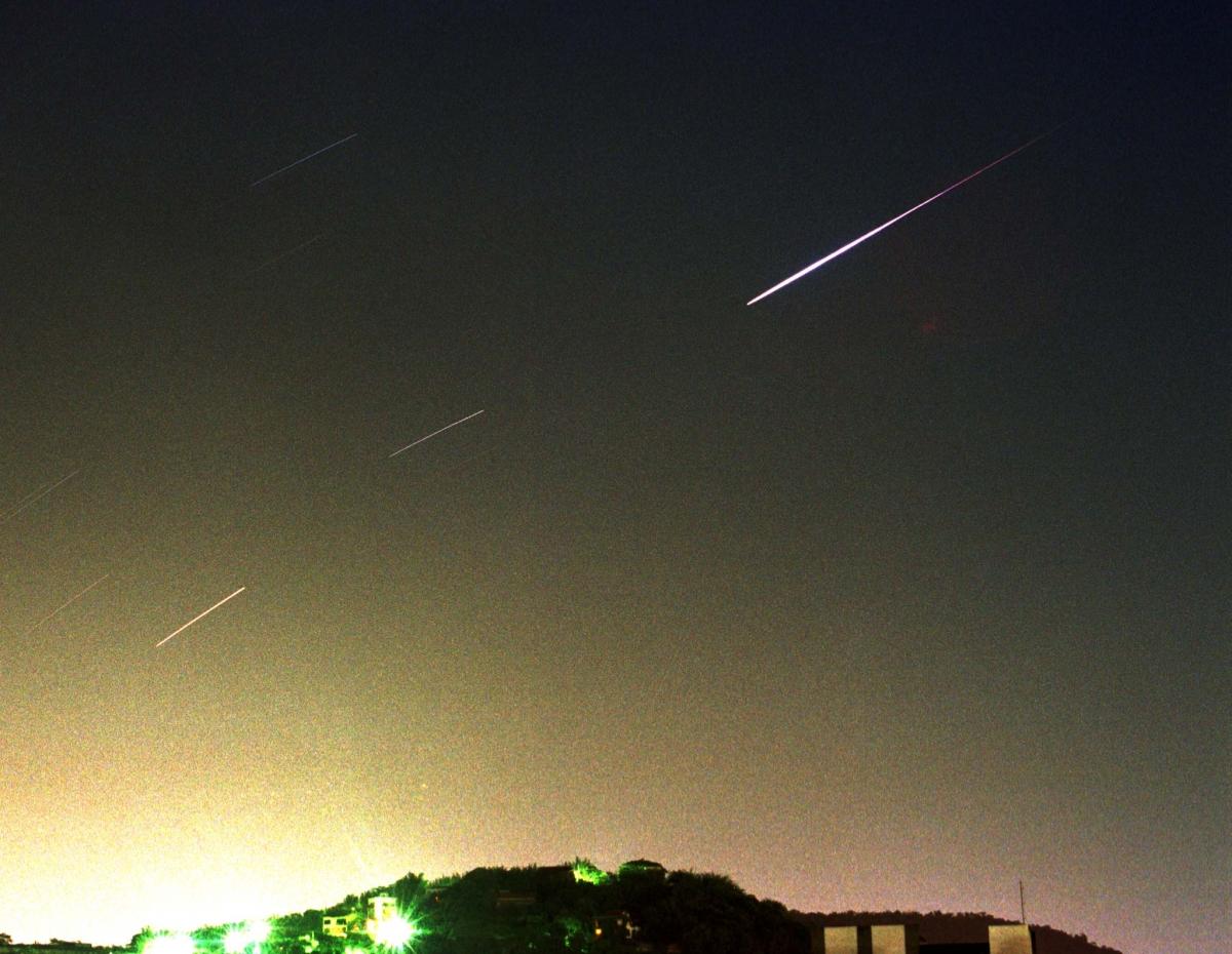 A meteor streaks across the night sky.