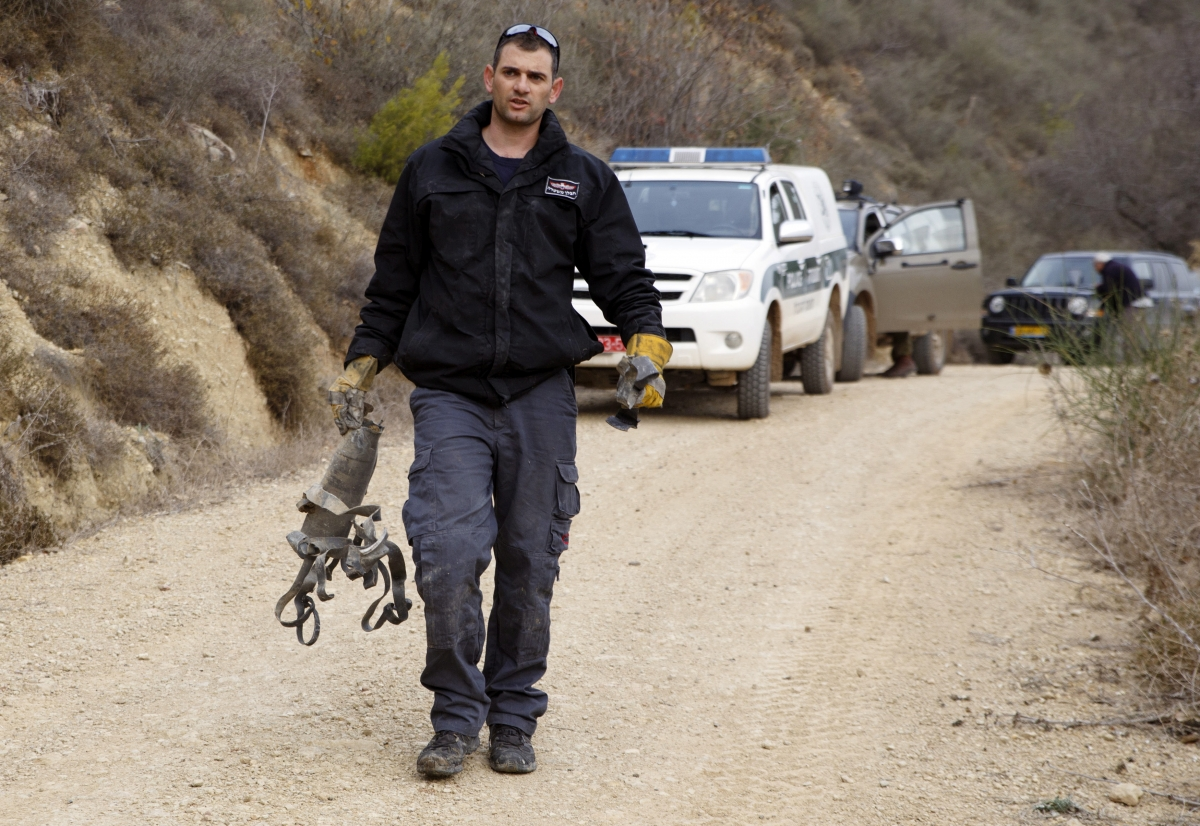 An Israeli police explosive expert carries the remains of a rocket after it landed near the northern town of Kiryat Shmona December