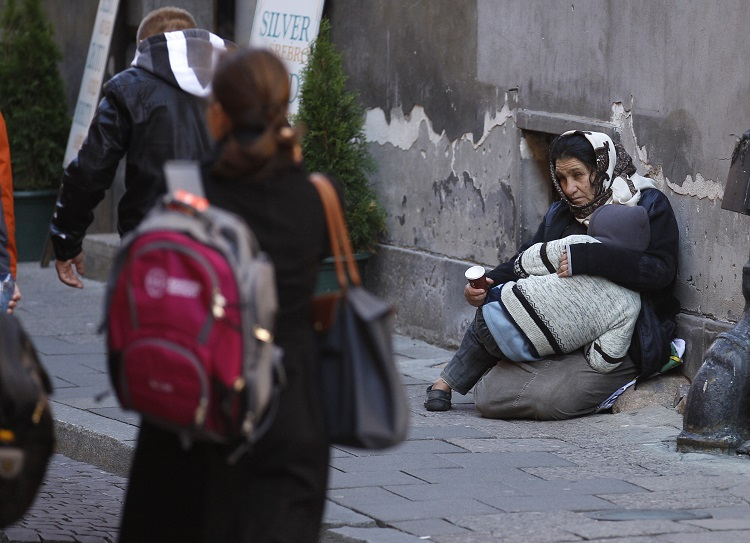 A Roma woman and her child beg for money