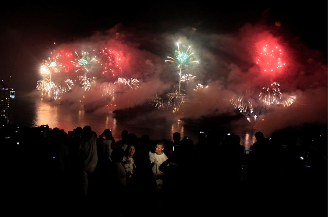 People watch fireworks exploding over Copacabana beach during New Year celebrations at the Pavao Pavaozinho slum in Rio de Janeiro.