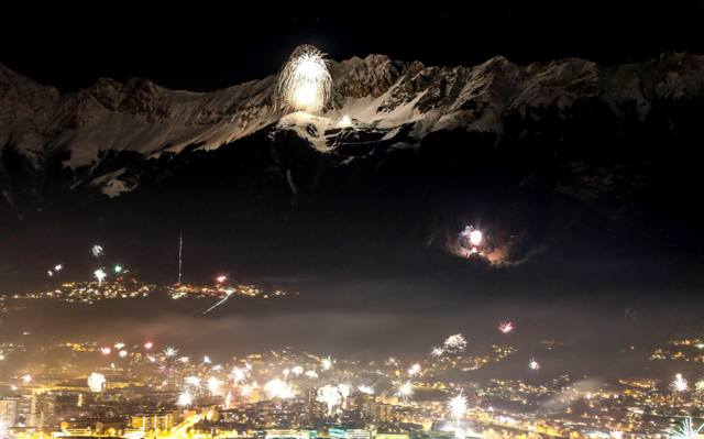 Fireworks explode over the city of Innsbruck and the Nordkette mountains during New Year celebrations.