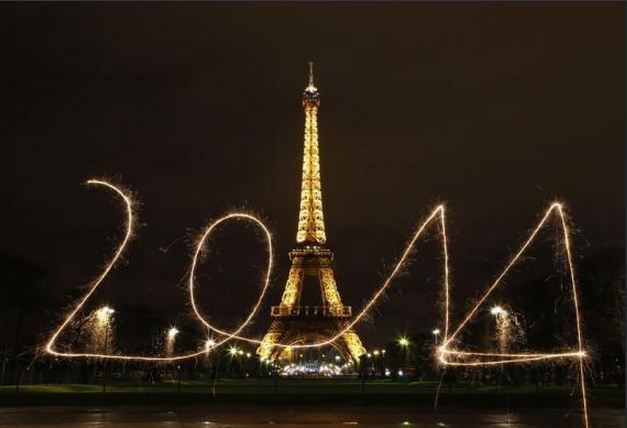 "A reveler writes ""2014"" with sparklers in front of the Eiffel Tower in Paris."
