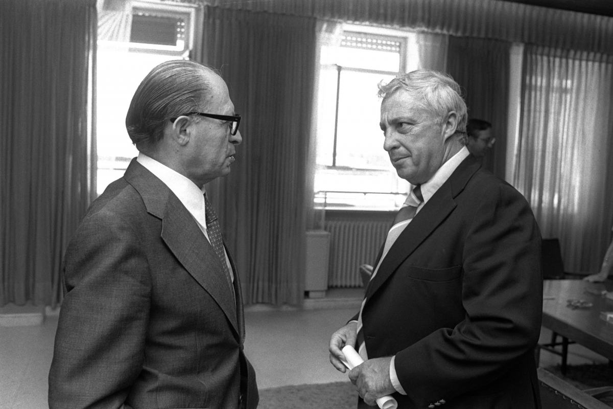 Israeli Prime Minister Menahem Begin (L) speaks with Ariel Sharon