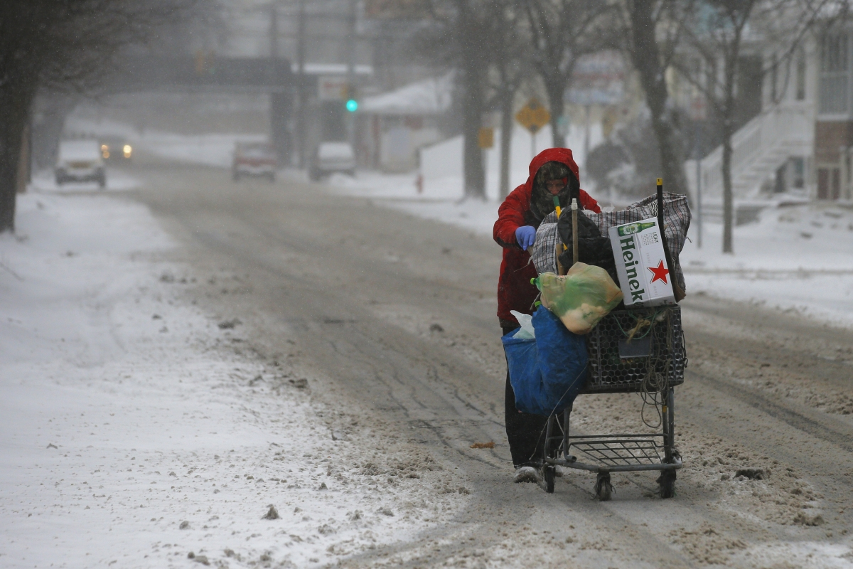 A man pushes a cart up the road while scavenging for bottles and cans during the storm.