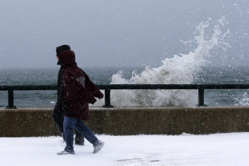 Onlookers walk past waves crashing against the seawall around high tide in Lynn following the storm.