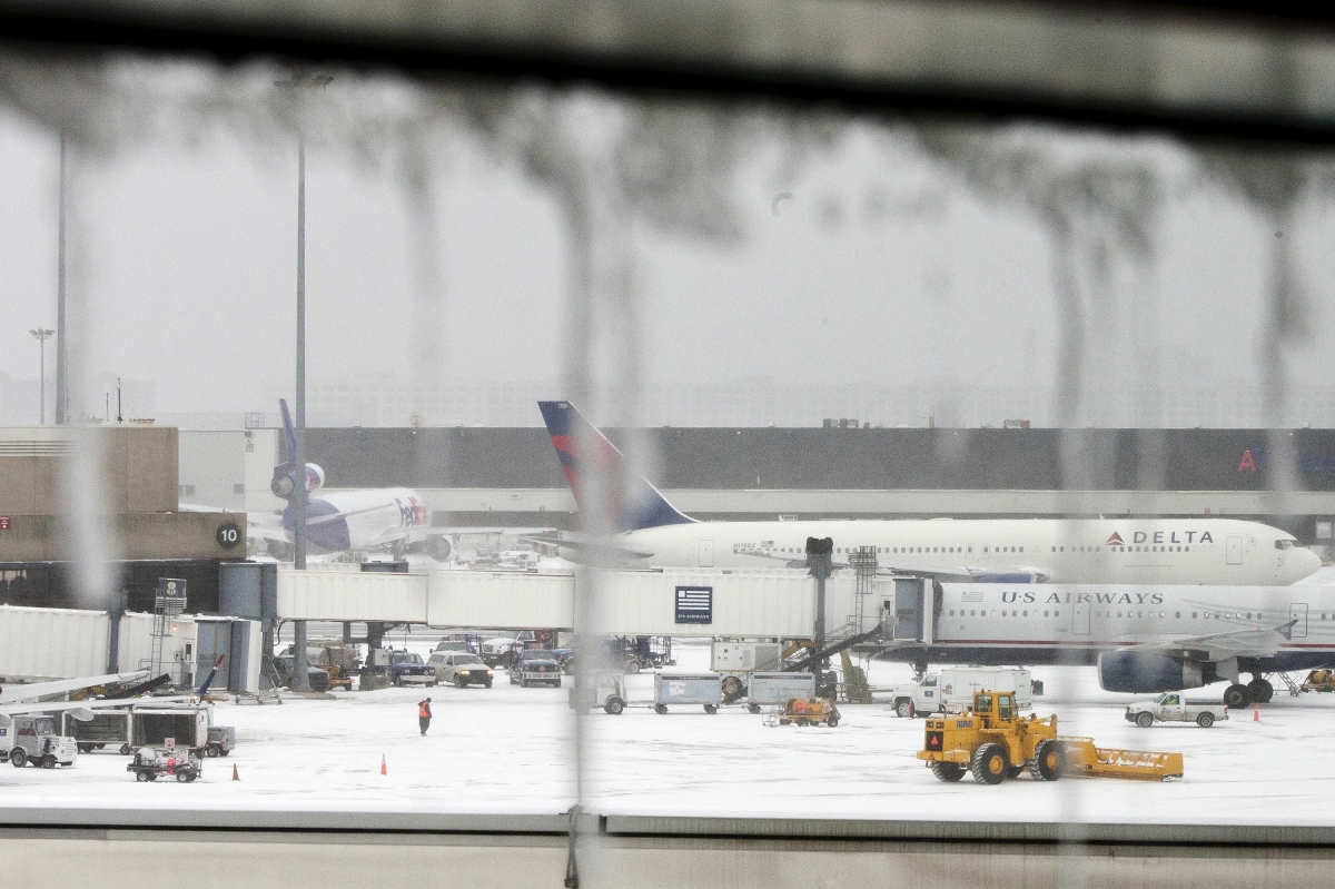 Icicles on a window are seen in front of airplanes during a winter nor'easter snow storm in Boston.