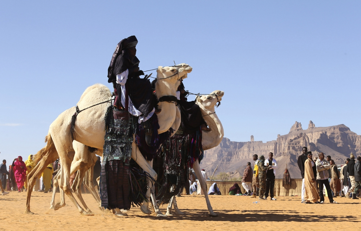 Tuareg men ride camels in the desert during the 19th Ghat Festival of Culture and Tourism.