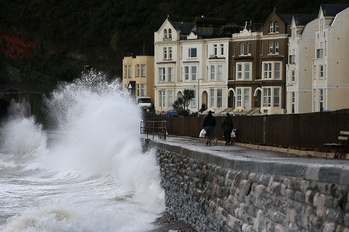 Waves crash against the promenade in Devon, south-east England.