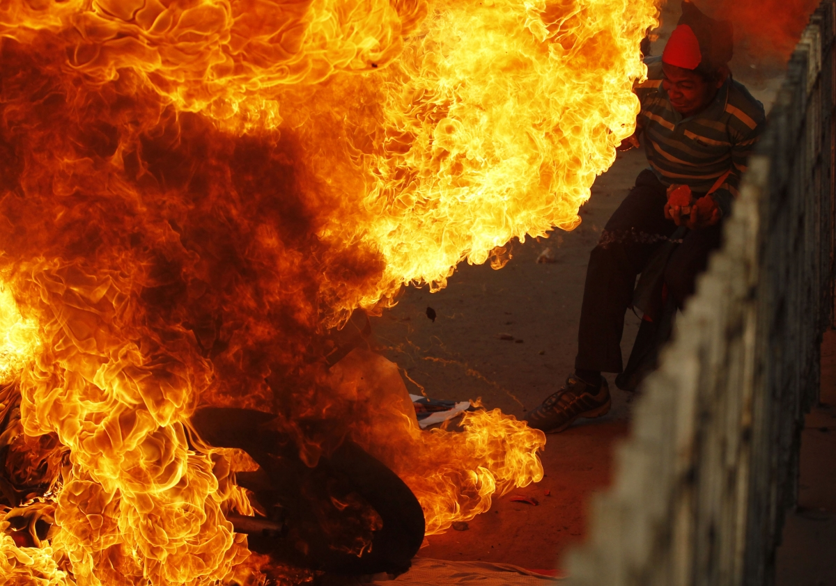 A pro-government activist sets fire to a motorcycle during a clash with Bangladesh National Party protesters in Dhakha on December 29.