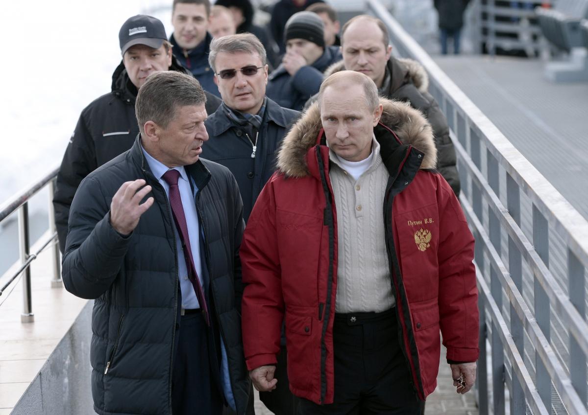 Russian President Vladimir Putin (R), Sberbank President German Gref (C) and Deputy Prime Minister Dmitry Kosak visit an Olympic venue near Sochi January 3, 2014.