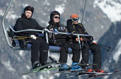 Russian President Vladimir Putin (L) and Prime Minister Dmitry Medvedev (C) sit on a chair lift during their visit to the