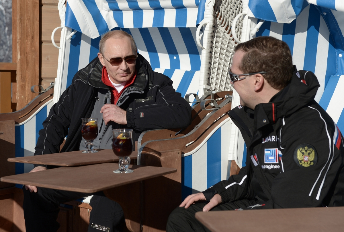 Russian President Vladimir Putin (L) and Prime Minister Dmitry Medvedev chat during their visit to the