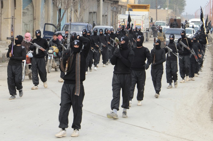 Isil fighters parade the streets of the Syrian town of Tel Abyad.
