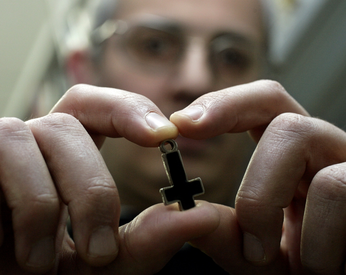 Professor at Rome's Regina Apolostolorum pontifical university holds an inverted cross used by Satanic worshippers.