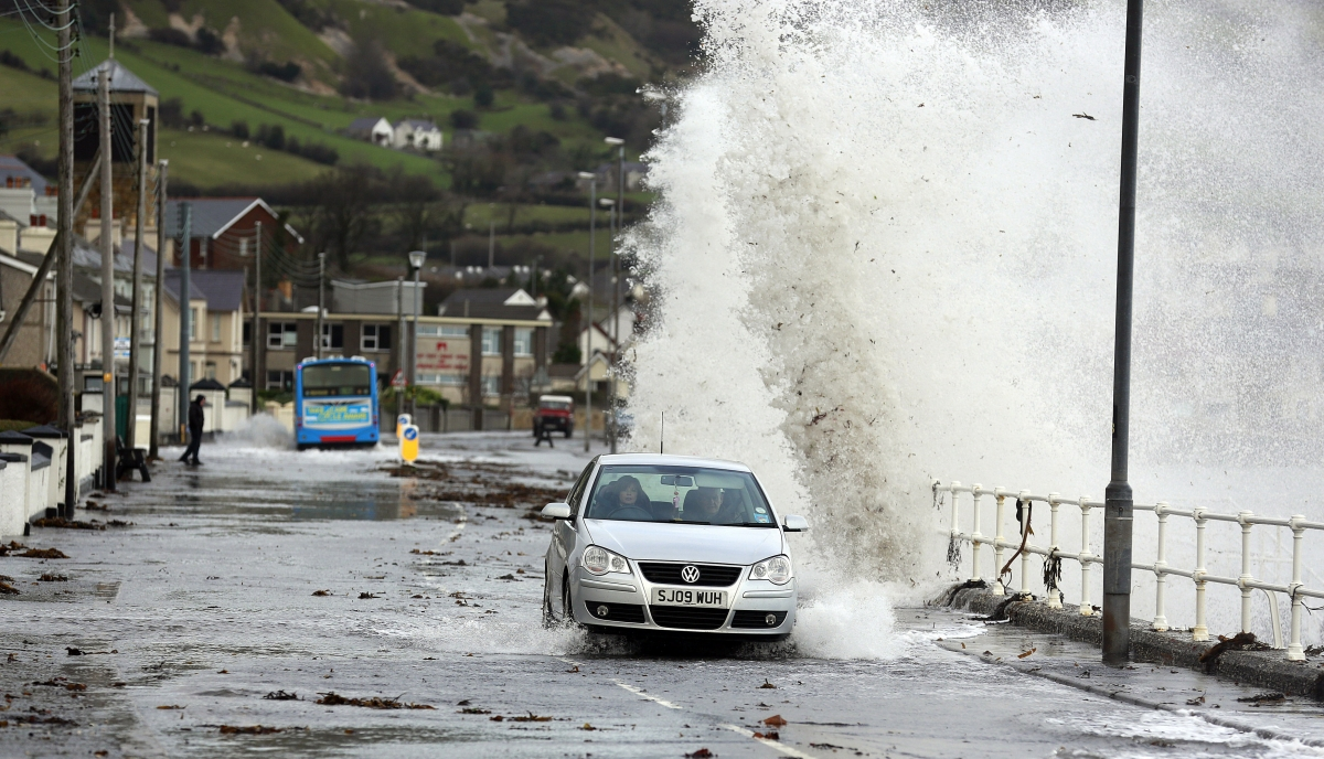 Waves crash against the coastal wall in the village of Carnlough as high tides and strong winds cause some flooding in coastal areas of Northern Ireland