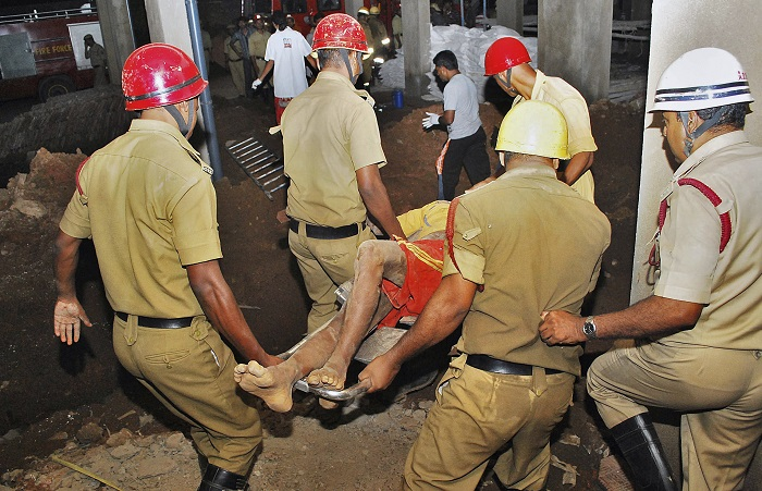 Rescuers carry an injured man away from the wreckage of Saturday's building collapse in Goa.