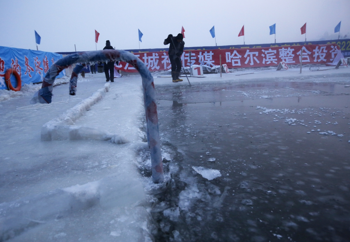 A worker breaks ice on a pool carved into the thick ice covering the Songhua River in China.