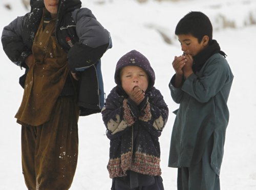 Children stand in the snow outside their shelter in Kabul, Afghanistan.