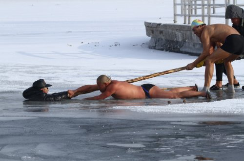 Winter swimmers try to pull an elderly man out of icy waters after he was trapped in a partially frozen lake at a park in Changchun, China.