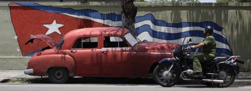 An army officer rides a motorcycle beside a US-made car used as a private collective taxi in Havana.