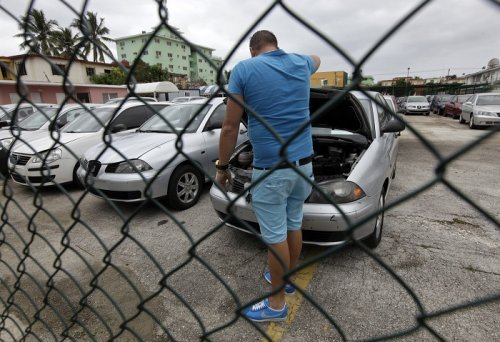 A man inspects a used car for sale at a vehicle dealership in Cuba's capital Havana.