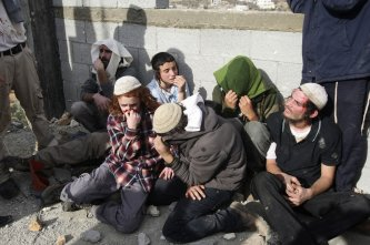 Jewish settlers sit together after being detained by Palestinian villagers