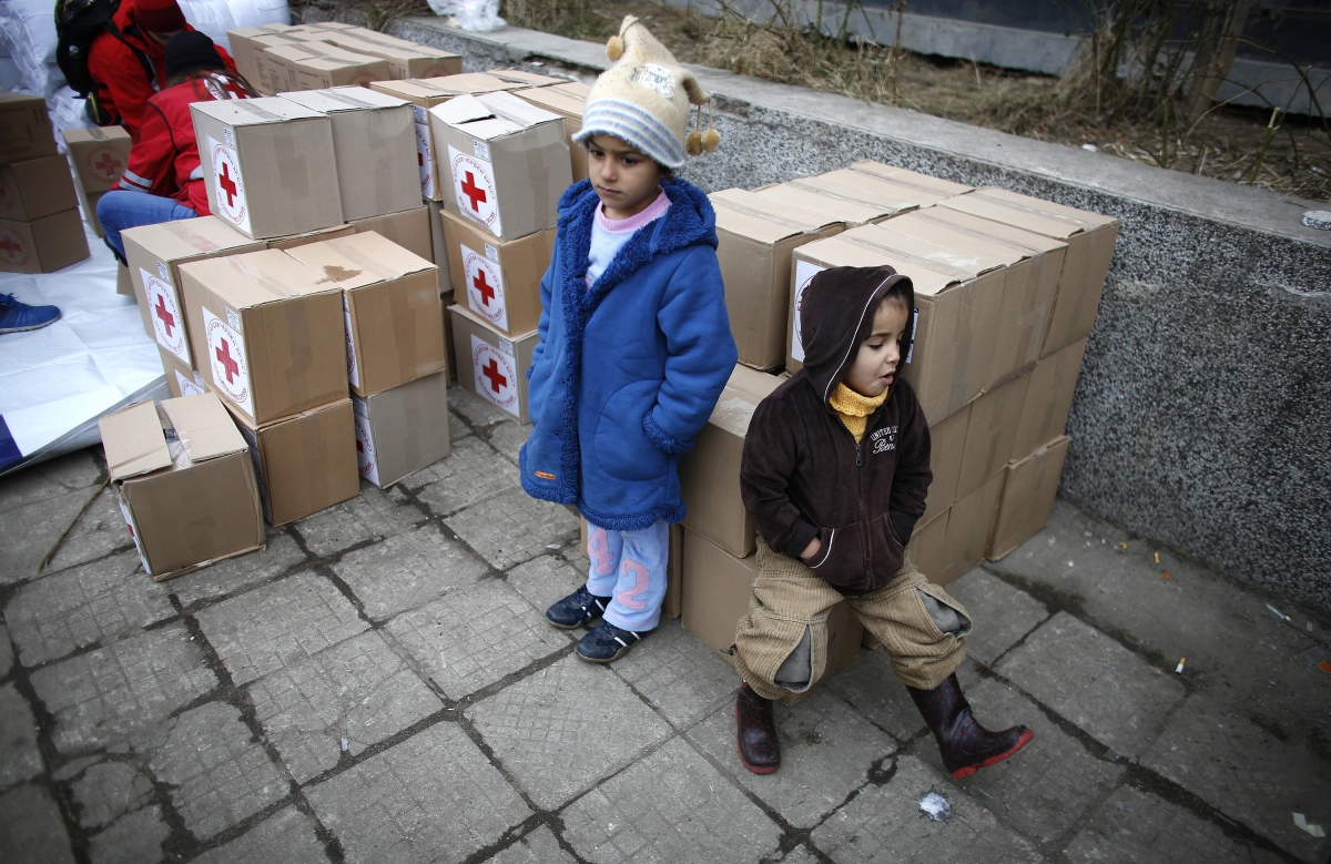 Syrian refugee children sit on boxes with humanitarian aid before its distribution by volunteers of the Bulgarian Red Cross